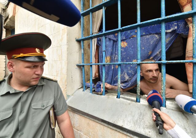 A prisoner speaks to the media from a prison cell in the Lukyanivska prison in Kiev next ot a prison officer during a press tour organized by the Ukrainian Ministry of Justice on July 19, 2016.