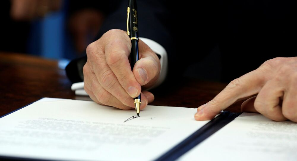 US President Donald Trump signs a memorandum to security services directing them to defeat the Islamic State in the Oval Office at the White House in Washington, US January 28, 2017