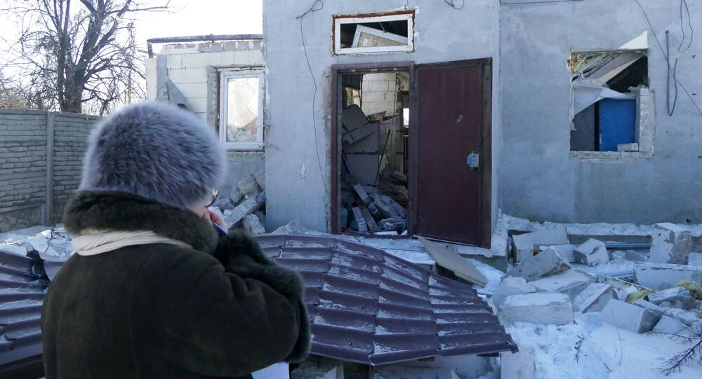 A woman by a house damaged by the shelling of the Ukrainian army in Makeevka, Donetsk Region