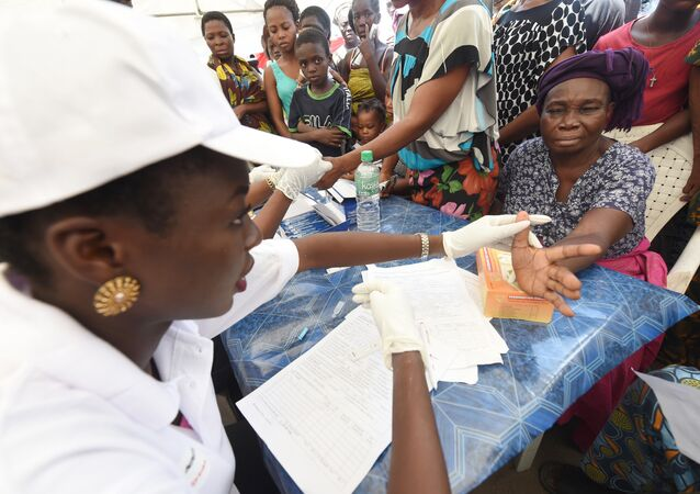 Health official takes blood sample of a woman for malaria testing at Ajah in Eti Osa East district of Lagos, on April 21, 2016.