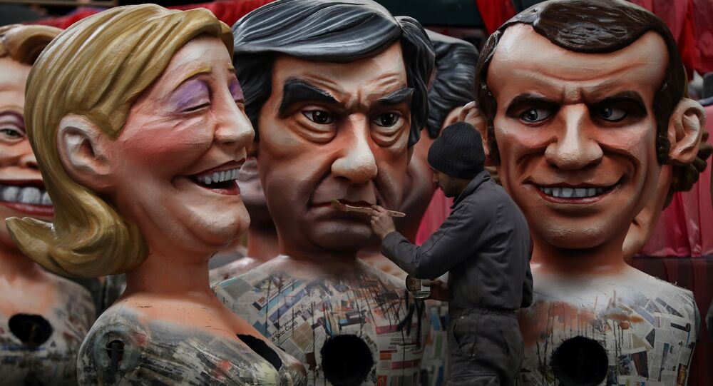 A man puts the final touche on a giant figure depicting right-wing presidential candidates Francois Fillon (C) next to others depicting far right presidential candidate Marine Le Pen (L) and centrist independent presidential candidate Emmanuel Macron, on January 27, 2017 in Nice, southeastern France.
