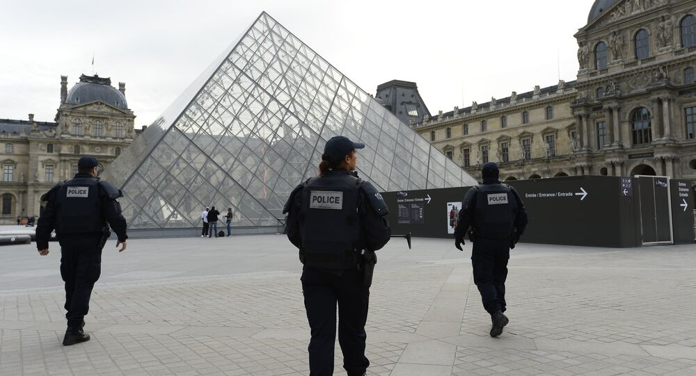 Police patrol in front of the Louvre Pyramid at the Louvre museum in Paris