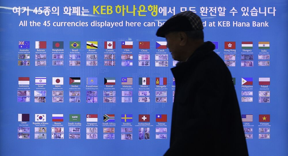 A man walks by a board displaying various banknotes issued in the world at a subway station in Seoul, South Korea.