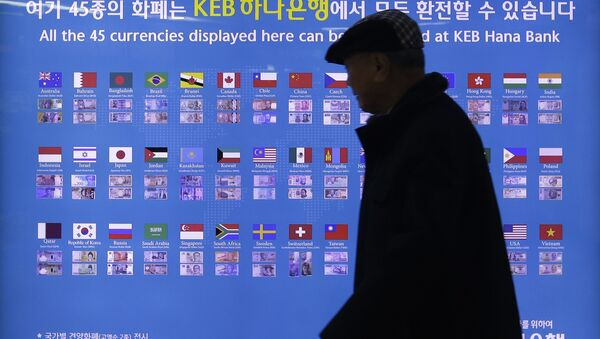 A man walks by a board displaying various banknotes issued in the world at a subway station in Seoul, South Korea. - Sputnik International