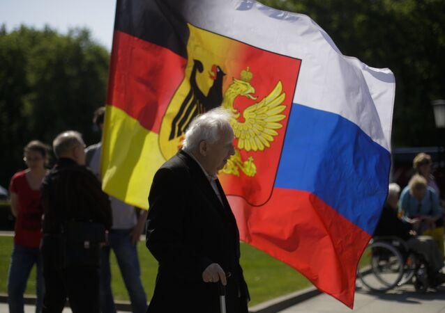 An old man stands in front of a combination of German and Russian national flags prior to a wreath laying ceremony at a Russian War Memorial to commemorate the end of World War II 71 years ago, at the district Tiergarten in Berlin, Germany, Monday, May 9, 2016