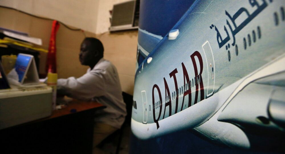 An image of a Qatar Airways plane is seen near an employee working at a travel agency in Khartoum, Sudan January 28, 2017