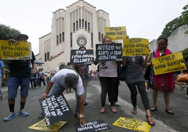 Human rights activists display placards outside the Baclaran Church prior to a mass in suburban Paranaque, south of Manila, Philippines.