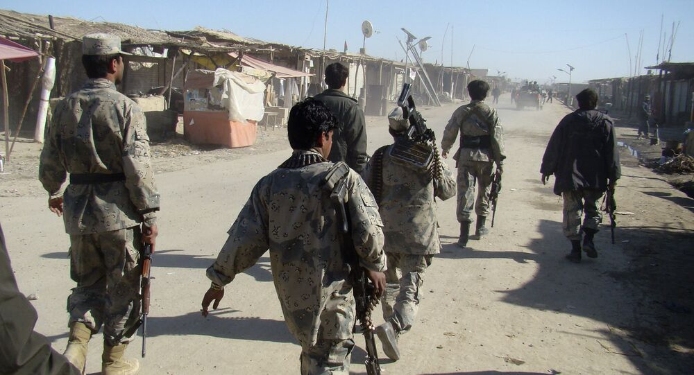 Afghan troops walk through the village of Laki , in Helmand province's Garmsir district, south of Kabul, Afghanistan (File)