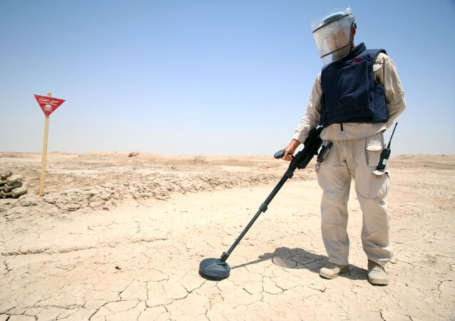 An Iraqi man wearing protective gear searches for landmines in the Shalamja border crossin, west of Basra, on the border between Iraq and Iran, on June 10, 2015