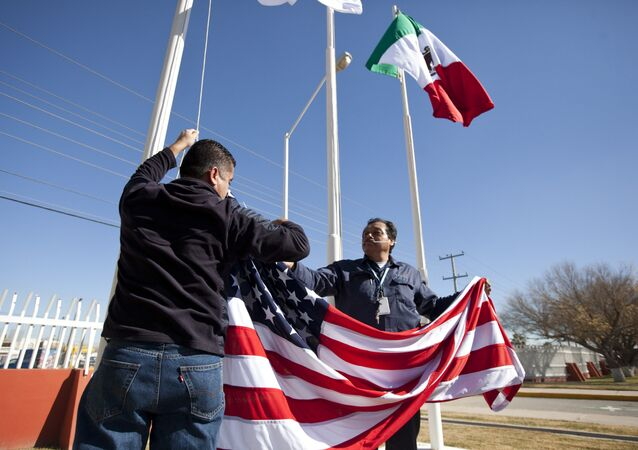 In this Friday, Dec. 27, 2013 photo, workers at one of maquiladoras of the TECMA group prepare to raise the U.S. flag along with the Mexican and TECMA flags in Ciudad Juarez, Mexico