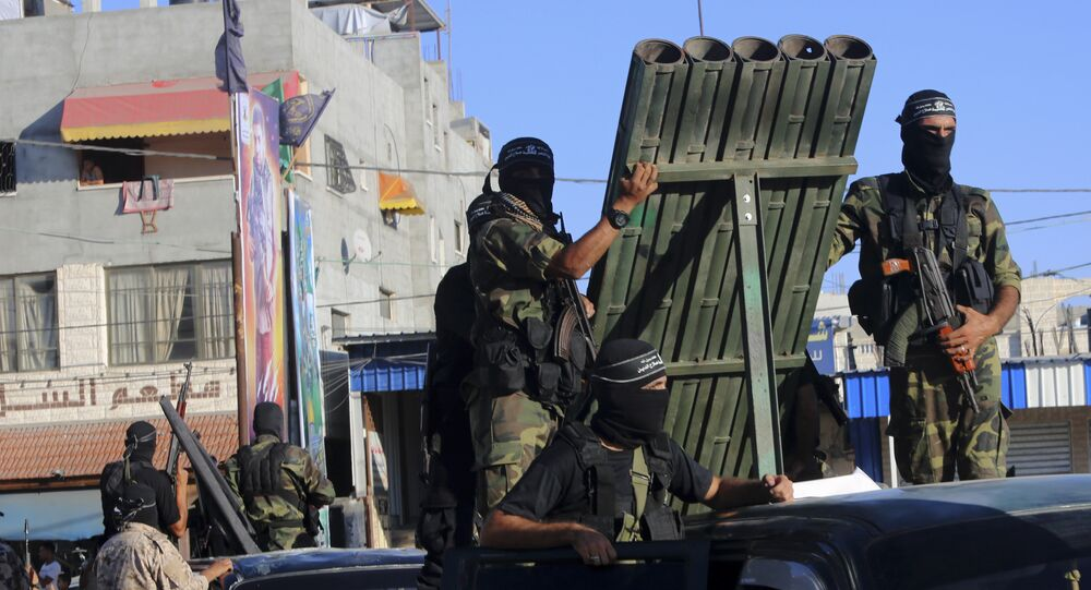 Palestinian militants from the al-Nasser Brigades, an armed wing of the Popular Resistance Committees (PRC), stand near rocket launcher while marching on their vehicles a long the streets during a rally to commemorate the 17th anniversary of their group in Rafah refugee camp, Gaza Strip, Monday, Sept. 26, 2016