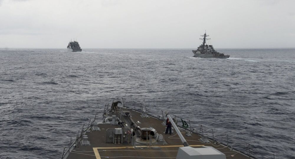 This image provided by the U.S. Navy, taken Oct. 17, 2016, shows the guided missile destroyer USS Decatur, right, pulling into position behind the Military Sealift Command USNS Matthew Perry, during a replenishment-at-sea, seen from the bridge of the guided-missile destroyer USS Spruance, in the South China Sea