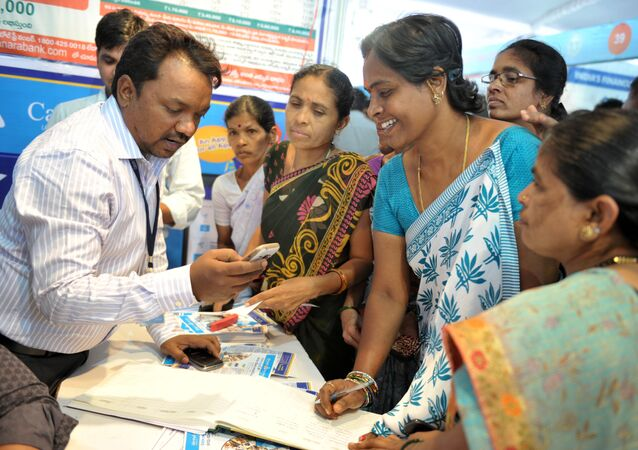 An Indian bank employee (L) explains to visitors about account transactions from a mobile phone with a Aadhaar or Unique Identification (UID) card during a Digi Dhan Mela, held to promote digital payment, in Hyderabad on January 18, 2017