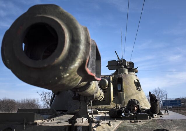 Ukrainian soldier smiles riding on a self-propelled artillery (File)