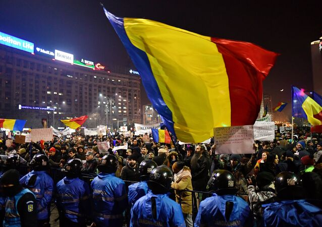 Romanian riot police stand guard as people demonstrate against controversial decrees to pardon corrupt politicians and decriminalize other offenses in front of the government headquarters in Bucharest, on February 1, 2017