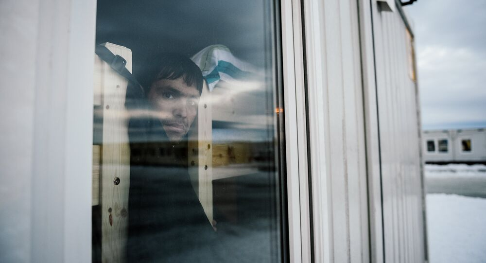 A refugee looks through a window in the sleeping facilities at the arrival centre for refugees near the town on Kirkenes in northern Norway close to the border with Russia on November 11, 2015