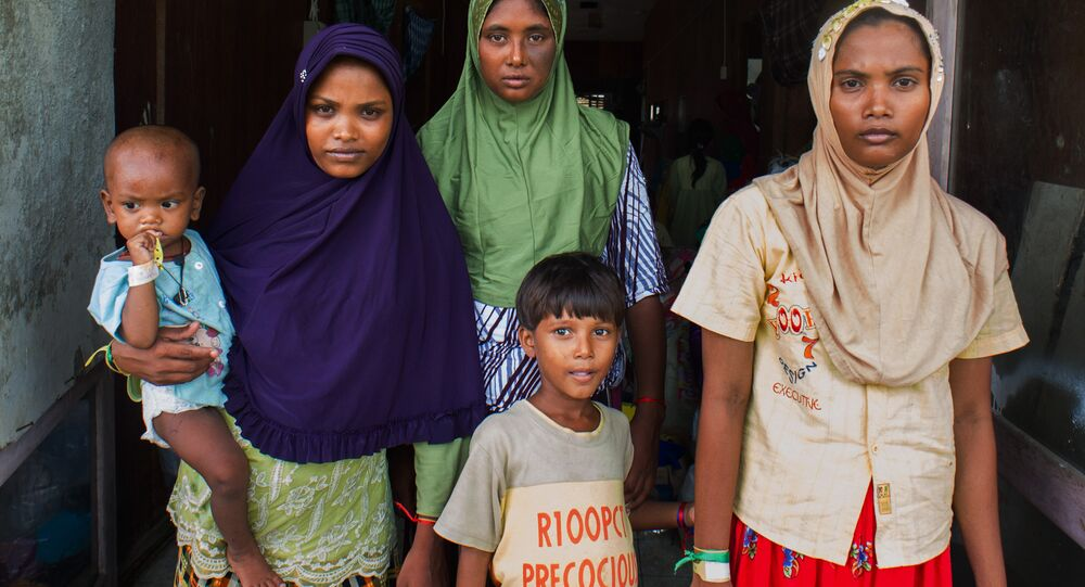 In this photograph taken on May 28, 2015, Rohingya migrant women from Myanmar (L-R) Rubuza Hatu, 21, Rehana Begom, 24 and Rozama Hatu, 23, stand at a confinement camp at Bayeun district in Indonesia's Aceh province after Indonesian fishermen rescued about 400 Rohingya migrants from Myanmar and Bangladesh from a boat on May 20, 2015 off the eastern coast of Aceh.