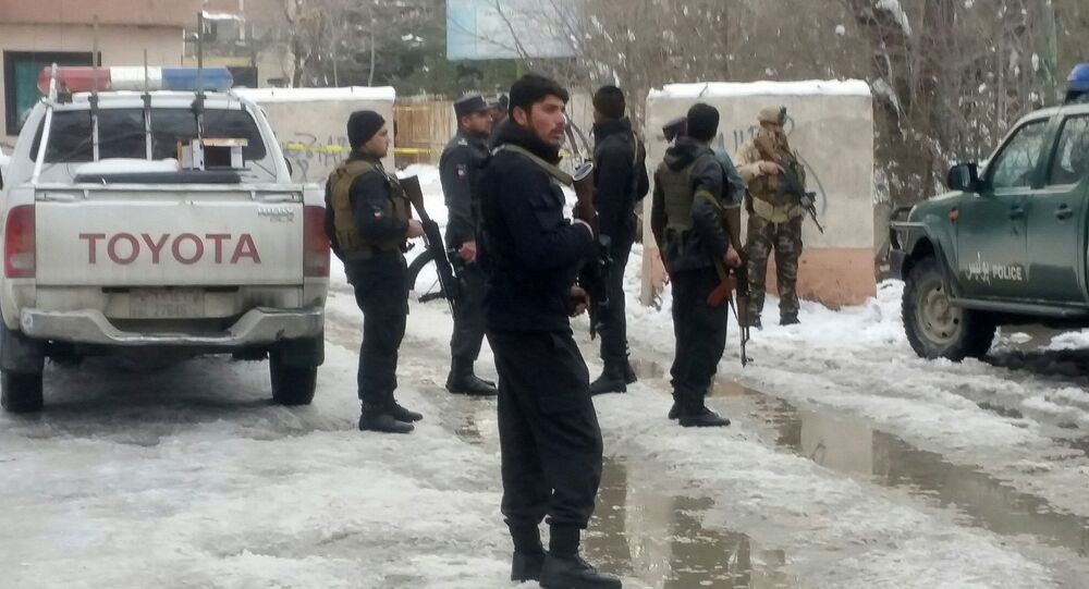 Afghan policemen keep watch at the site of a bomb blast in Kabul, Afghanistan