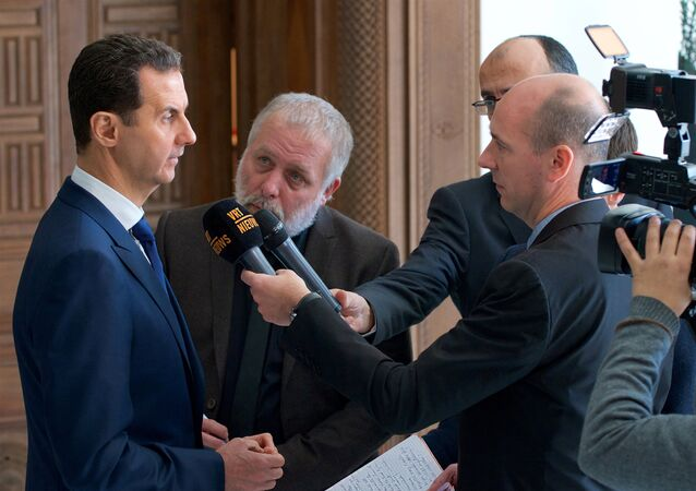 Syria's President Bashar al-Assad speaks to a group of Belgian reporters in this handout picture provided by SANA on February 7, 2017, Syria