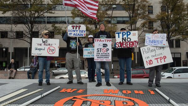 People hold signs as they demonstrate against the Trans-Pacific Partnership (TPP) trade agreement in Washington, DC, on November 14, 2016 - Sputnik International