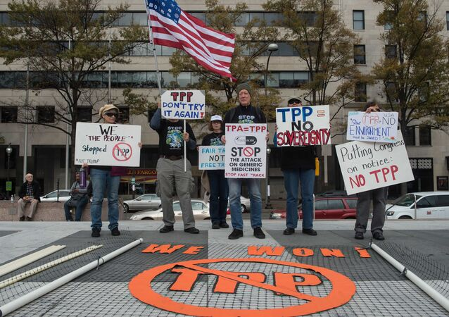 People hold signs as they demonstrate against the Trans-Pacific Partnership (TPP) trade agreement in Washington, DC, on November 14, 2016