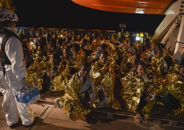 Migrants and refugees wrapped in survival foil blankets rest during a rescue operation by the Topaz Responder ship, run by Maltese NGO Moas and the Italian Red Cross, on November 4, 2016