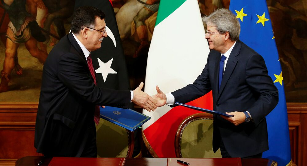 Italian Prime Minister Paolo Gentiloni (R) and his Libyan counterpart Fayez al-Sarraj shake hands after signing a bilateral agreement during a meeting at Chigi Palace in Rome, Italy February 2, 2017.