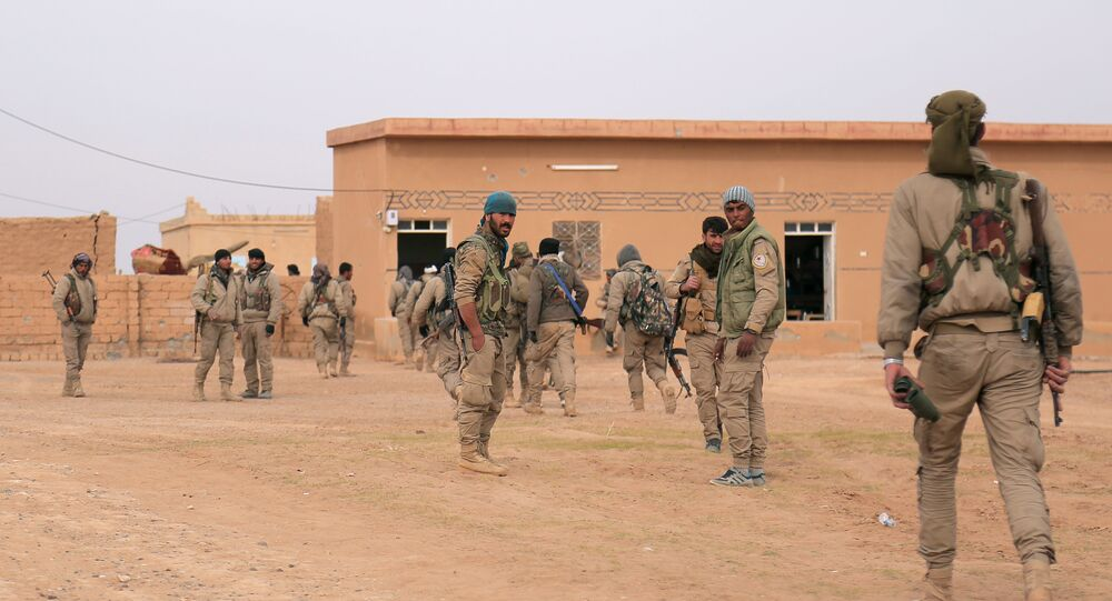 Syrian Democratic Forces (SDF) fighters walk with their weapons during an offensive against Daesh terrorists in northern Raqqa province, Syria