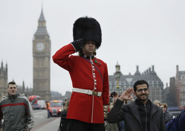 A man on stilts dressed in a ceremonial guardsman costume poses for photographs for tourists as he hands out flyers and collects money for charity on the southern end of Westminster Bridge backdropped by the Houses of Parliament in London, Wednesday, February 8, 2017.