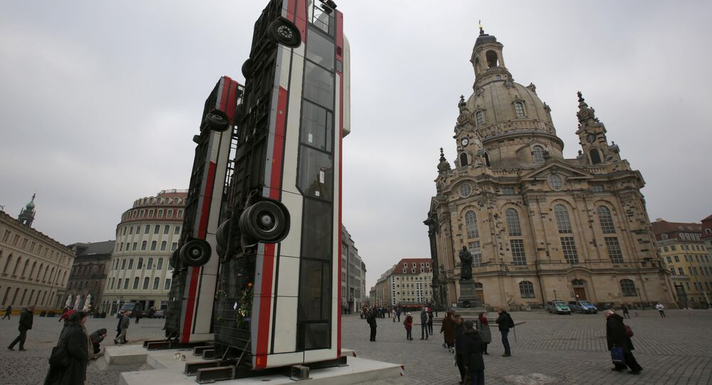 People walk next to the art instalation Monument by Syrian artist Manaf Halbouni, made from three passenger busses in Dresden, Germany February 8, 2017.