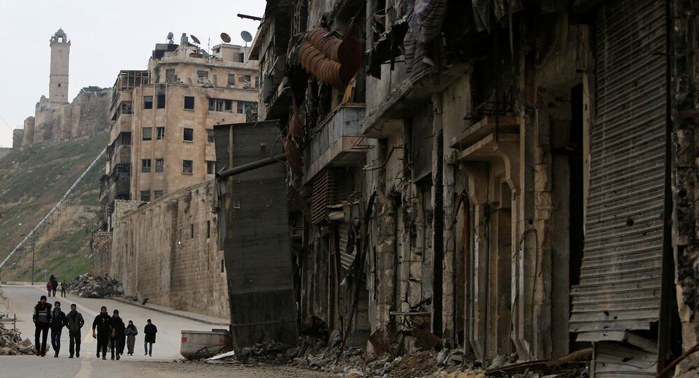People walk past damaged shops in the Old City of Aleppo, Syria January 31, 2017.