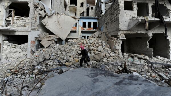 A man walks near damaged buildings in Aleppo, Syria January 30, 2017. - Sputnik International