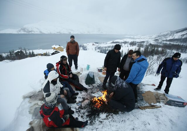 Asylum seekers gather round a fire as they cook a meal overlooking the temporary Altnes camp refugee camp on the island of Seiland, northern Norway