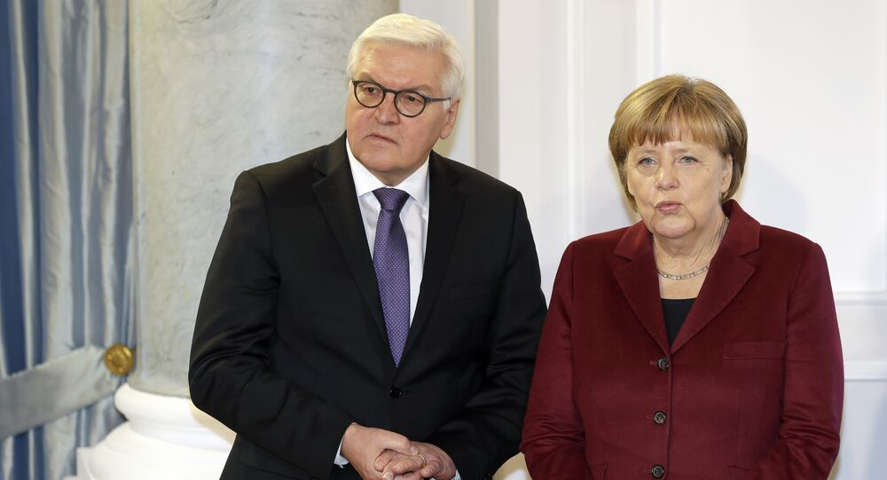 German Chancellor Angela Merkel, right, and German Foreign Minister Frank-Walter Steinmeier, left, talk as they pose for the media during a New Year's reception of German President Joachim Gauck at the Bellevue palace in Berlin, Germany, Tuesday, January 10, 2017.