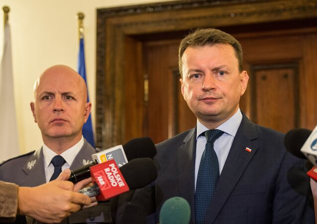 Poland's Interior Minister Mariusz Blaszczak (R) speaks during a press conference at the Polish Embassy in London. (File)