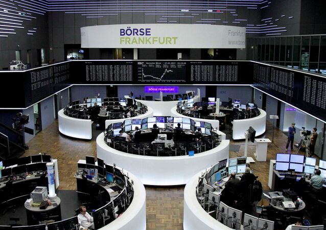Traders work at their desks in front of the German share price index, DAX board, at the stock exchange in Frankfurt, Germany, January 17, 2017