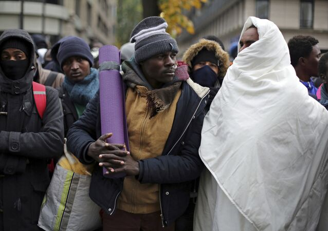 Migrants wait to board buses to temporary shelters in Paris, Friday, Nov. 4, 2016