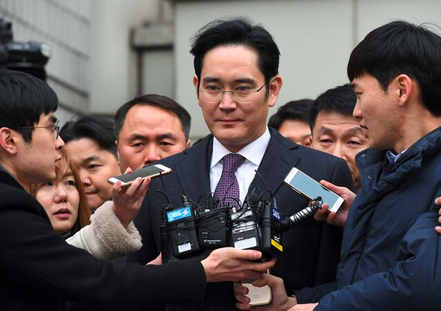 Samsung Group's heir-apparent Lee Jae-Yong (C) leaves for a waiting facility after attending a court hearing on whether he will be issued with an arrest warrant at the Seoul Central District Court in Seoul on January 18, 2017
