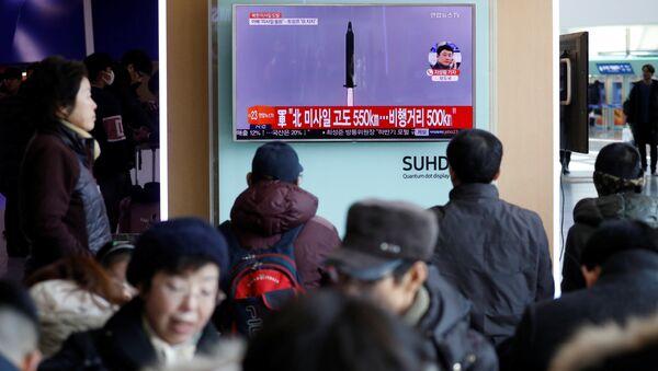 Passengers watch a TV screen broadcasting a news report on North Korea firing a ballistic missile into the sea off its east coast, at a railway station in Seoul, South Korea, February 12, 2017 - Sputnik International