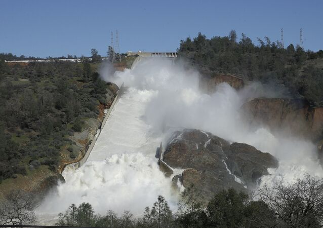 In this Saturday, Feb. 11, 2017, water flows down Oroville Dam's main spillway near Oroville, Calif.