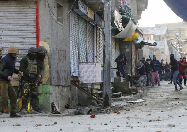 Masked Indian Kashmiri protestors (R) throw stones towards Indian government forces during clashes after Friday congregation prayers against Indian rule outside the grand mosque Jamia Masjid in downtown Srinagar on February 9, 2017