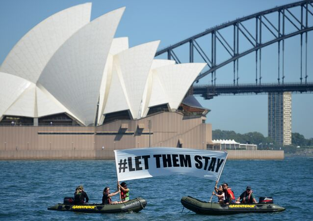 Members of the environmental group Greenpeace hold up a sign that reads #LET THEM STAY in front of the Opera House in Sydney on February 14, 2016.
