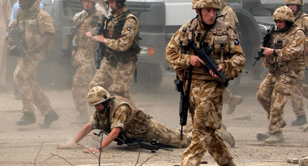 In this May 6 , 2006 file photo, a British trooper falls after apparently being hit by a rock, as British troops move towards a helicopter crash site in Basra, Iraq's second-largest city, 550 kilometers (340 miles) southeast of Baghdad. Britain's prime minister announced plans on Oct. 4, 2016 to protect British troops from dubious legal claims made during conflicts.
