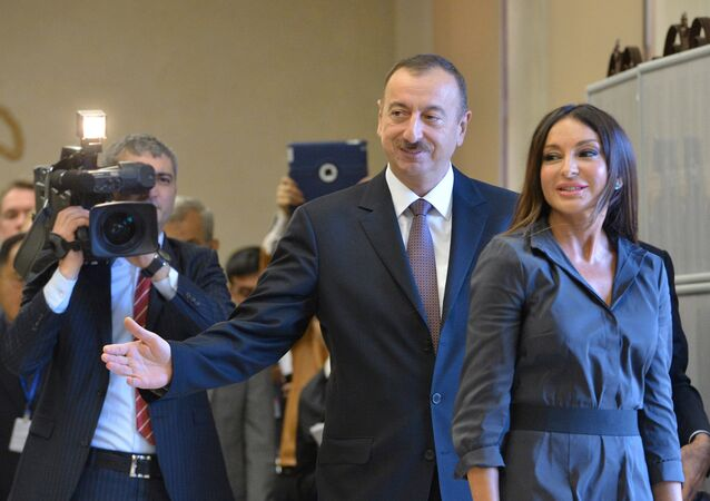 Incumbent Azerbaijani President Ilham Aliyev with his wife, Merhiban, voting at a polling station in Baku during the presidential elections