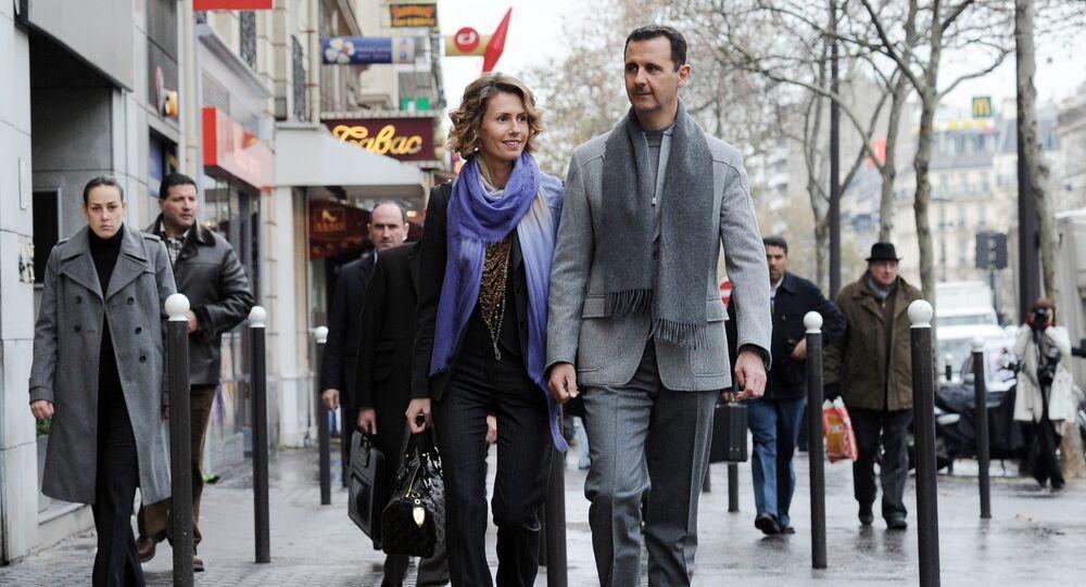 Syrian president Bashar al-Assad and his wife Asma walk in a Parisian street on 10 December 2010.