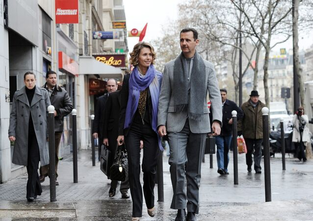Syrian president Bashar al-Assad and his wife Asma walk in a street of Paris on December 10, 2010