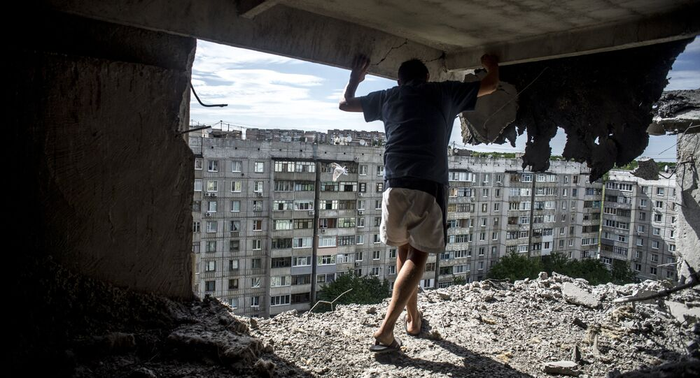 Man inspects damaged residential building in the Mirny district of Lugansk, hit by artillery fire. File photo