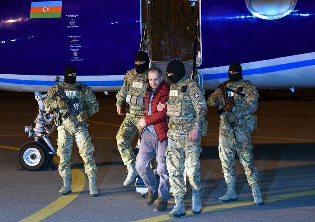 Russian-Israeli blogger Alexander Lapshin, center, who was extradited from Minsk upon Baku's request, at Heydar Aliyev International Airport