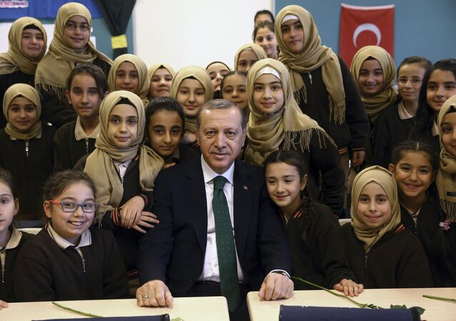 Turkey's President Recep Tayyip Erdogan poses for a photo with students of a religious girl school in Istanbul, Saturday, Dec. 10, 2016.