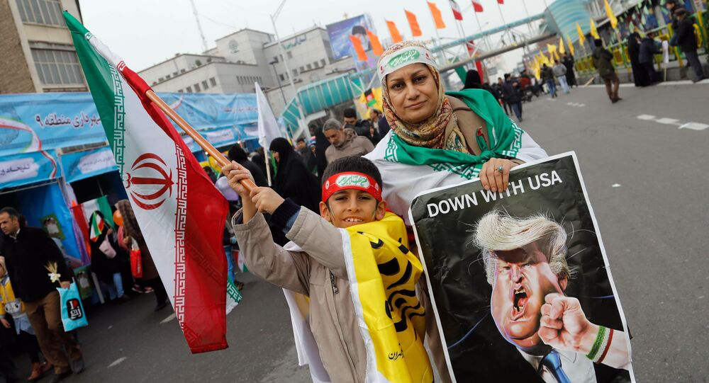 An Iranian woman holds a placard showing a caricature of US President Donald Trump being punched by a hand wearing a bracelet of the Iranian flag during a rally marking the anniversary of the 1979 Islamic revolution on February 10, 2017, in the capital Tehran
